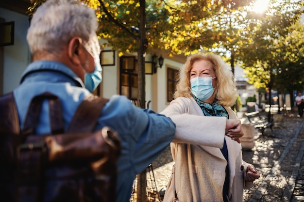 Senior friends with protective masks on standing outdoors and greet with their elbows.
