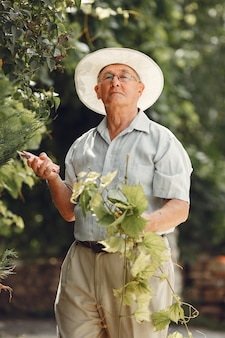 Il giardiniere senior sta godendo il suo lavoro in giardino. vecchio con una camicia bianca.