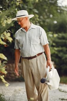 수석 정원사는 정원에서 그의 일을 즐기고 있습니다. 흰 셔츠에 늙은이.