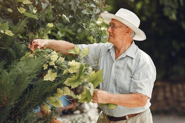 Старший садовник наслаждается своей работой в саду. старик в белой рубашке.