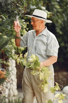 先輩の庭師は庭で仕事を楽しんでいます。白いシャツを着た老人。