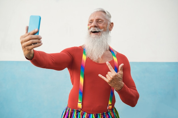 Lgbt 프라이드 시위 중 휴대 전화를 사용하는 수석 게이 남자-얼굴에 초점