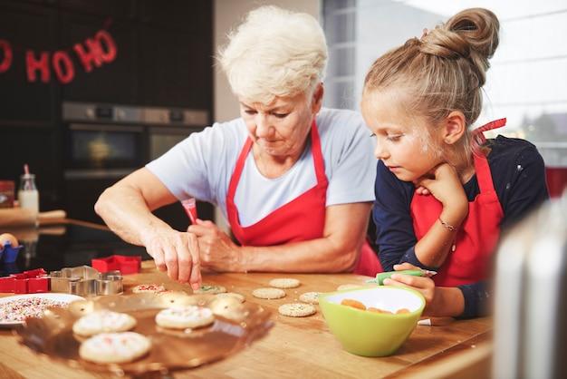 Anziano e ragazza che preparano i biscotti di natale