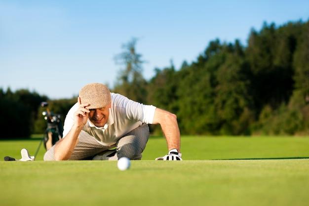 Senior golf player looking at a ball