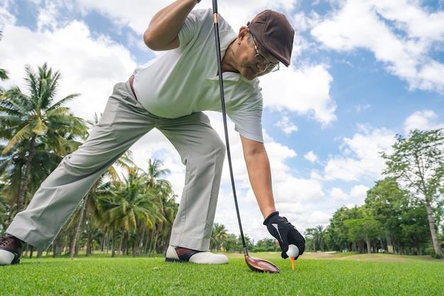 Старший игрок в гольф, играющий в гольф на профессиональном поле для гольфа.