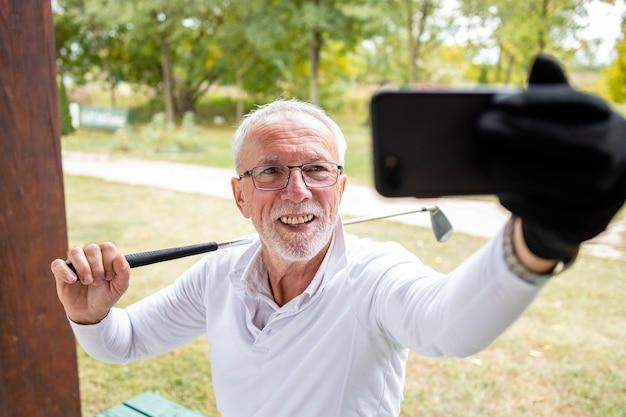 Старший игрок в гольф, делающий селфи после тренировки для социальных сетей.