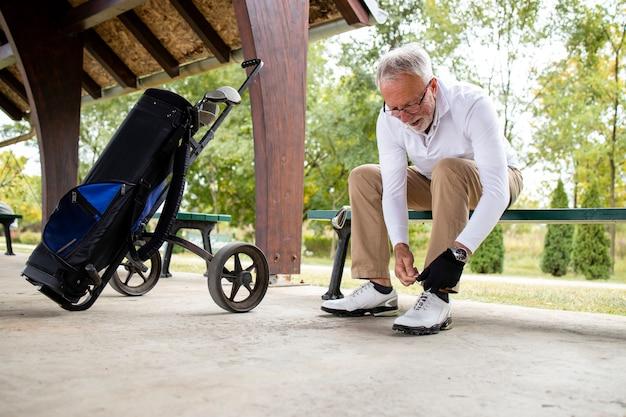 Старший игрок в гольф завязывает шнурки перед тренировкой в гольф.