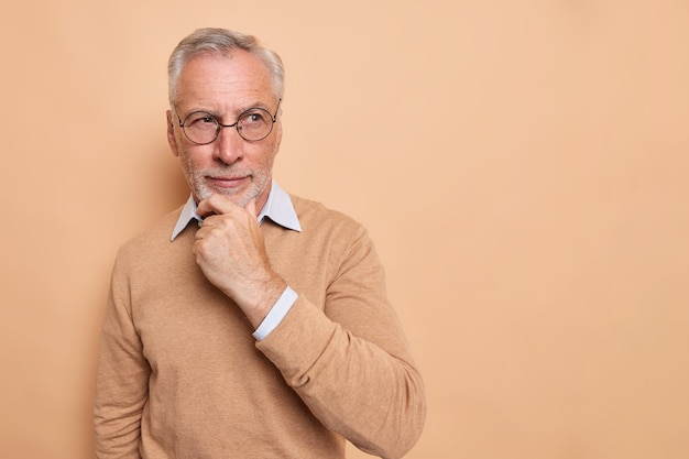 Senior grandfather stands in thoughtful pose holds chin looks into distance