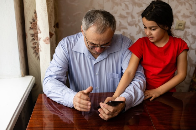 Senior grandfather with child girl granddaughter spending time home together, sitting in living room, using digital mobile phone. watching videos, playing games, social network