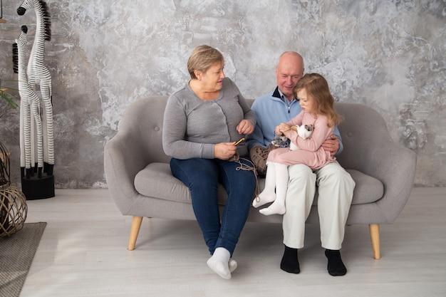 シニアの祖母と祖父が家族の家で彼女の孫娘と一緒に編み物をしています。リビングルームのソファーに座っているかぎ針編みの小さな女の子を持つ女性