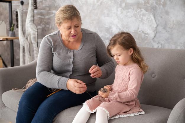 家族の家で孫娘と一緒に編み物をするシニアの祖母。リビングルームのソファーに座っているかぎ針編みの小さな女の子を持つ女性