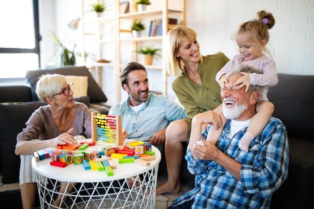 Старшие бабушка и дедушка играют с внуками и веселятся с семьей