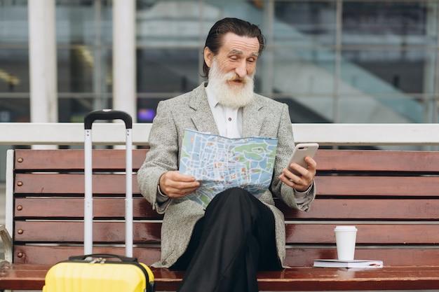 Старший седобородый мужчина сидит рядом на скамейке с чемоданом, смотрит карту города и телефон у здания аэропорта