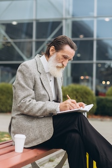 Senior gray-bearded man with carrying suitcase and city map sits and write notes in notebook along the airport building