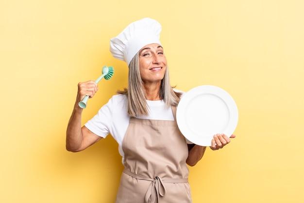 シニア白髪の女性。食器洗いのコンセプト
