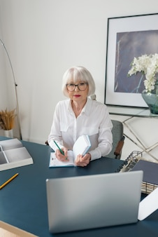 Senior gray hair woman in white blouse reading documents in office