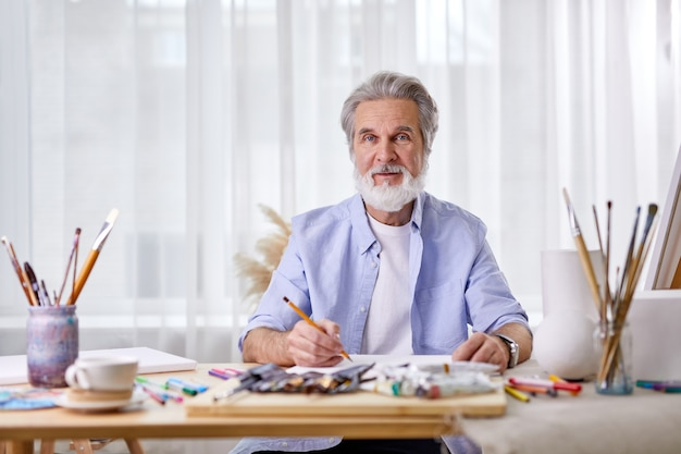Senior gray haired artist with pencil sitting behind table ready to paint something, having different tools, paper and other materials for drawing