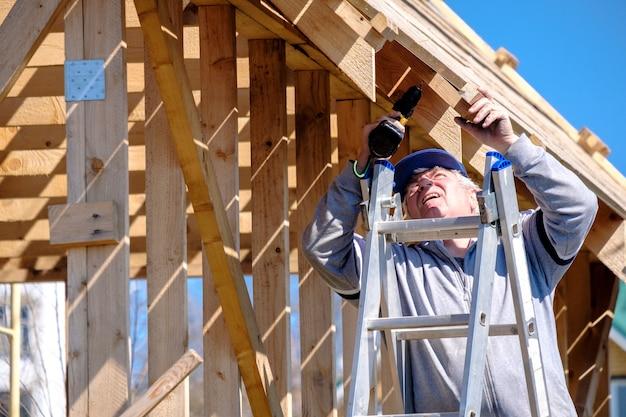 수석 회색 머리 빌더는 목조 시골집의 프레임을 수집