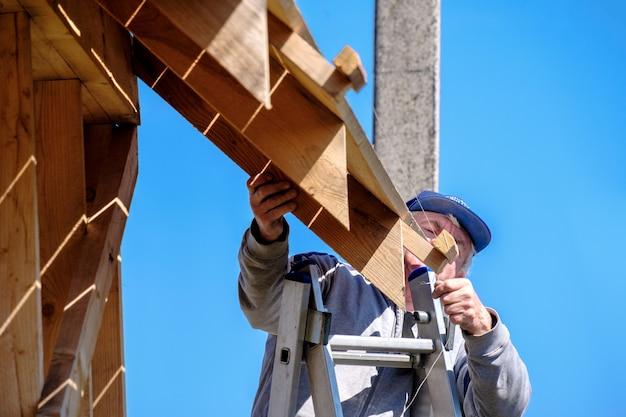 Старший седой строитель спускается по лестнице на фоне голубого неба