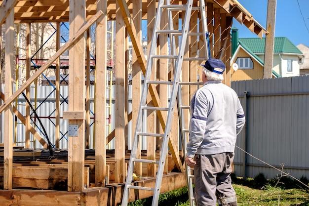 서 있는 시골집의 프레임을 검사하는 수석 백발 건축업자