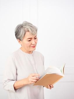 Старшие седые волосы азиатская женщина держа и читая книгу дома.