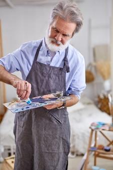 家で、趣味として働く画家パレットと帆布を使用して絵を描くシニア白髪のアーティストの男