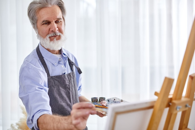 Senior grey haired artist man painting using painter palette and canvas, at home, work as hobby