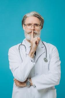 Стетоскоп старшего седого доктора человека нося стоя над изолированной голубой стеной прося быть тихим с пальцем на губах. молчание и секретная концепция.