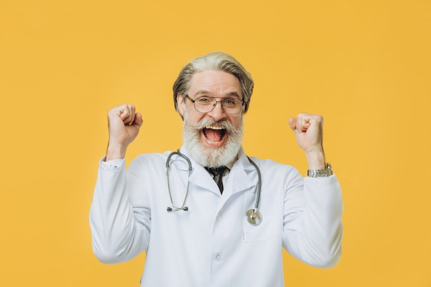 Стетоскоп старшего седого доктора человека нося стоя над изолированным желтым праздновать стены счастливый и изумленный для успеха с поднятыми оружиями и открытыми глазами. концепция победителя.