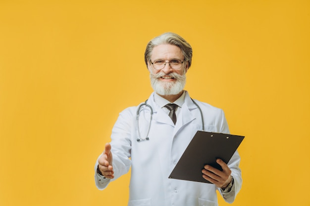 Стетоскоп старшего седого доктора человека нося стоя над изолированной желтой стеной