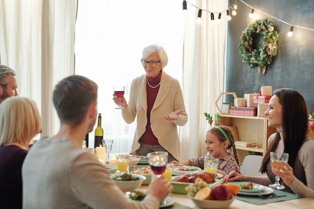 Пожилая седовласая женщина поджаривает тосты с бокалом красного вина за сервированным столом перед своей семьей во время соблазнительного ужина