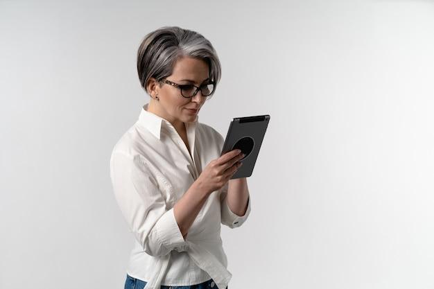 Старшая седая женщина в белой рубашке с помощью цифрового планшета. использование техники пожилыми людьми