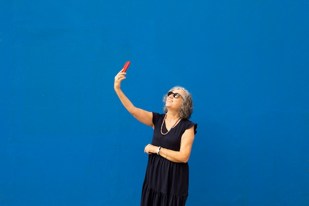 Senior grey haired woman taking a selfie with a red smartphone against a blue wall