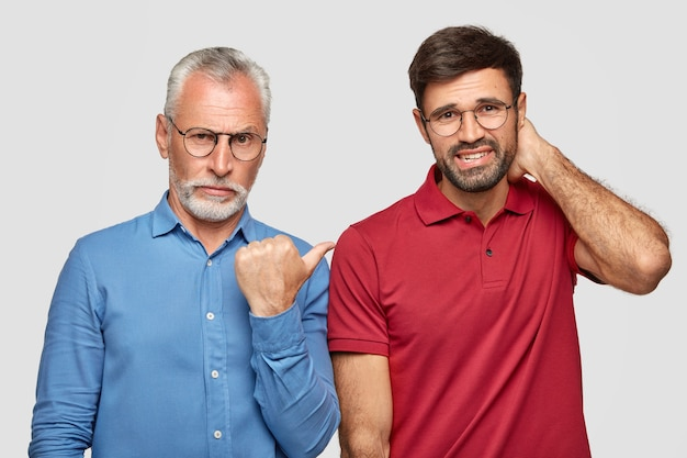 Senior grey haired young male with serious expression indicates with thumb at his young business partner who has nervous expression, stand closely to each other, isolated over white wall