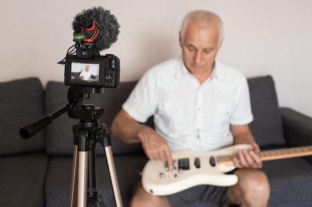 インターネットvlogウェブサイトクラスのビデオレッスンとチュートリアルを作成するシニアギタリスト