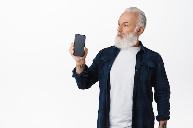 Senior guy looks surprised at smartphone screen, showing mobile phone application or webpage on display, standing amazed against white wall