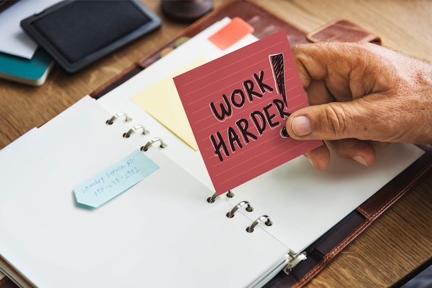 Senior hand holding a work harder sticky note