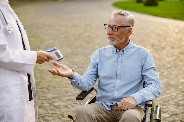 Senior handicapped man reaching out hand for doctor to check fever by digital thermometer scanning