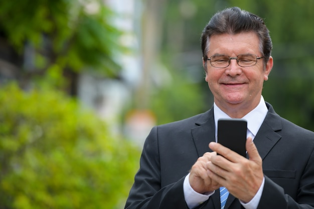 Senior handsome businessman smiling while using phone