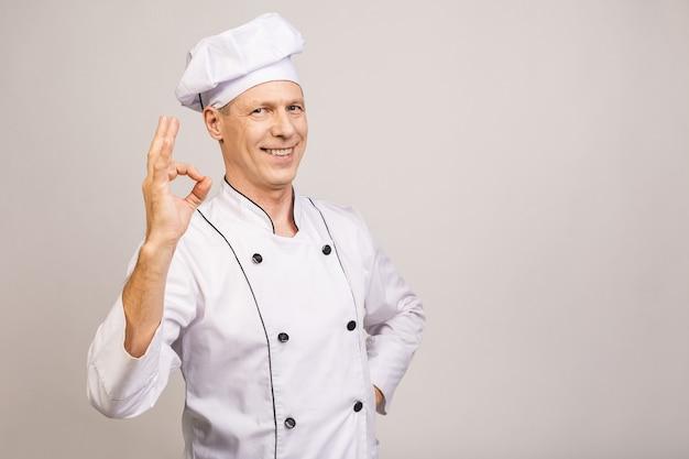灰色の壁に分離されたシニアのハンサムなシェフ料理。わかりました。