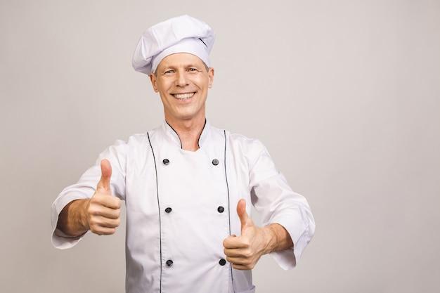 灰色の壁に分離されたシニアのハンサムなシェフ料理。いいぞ。