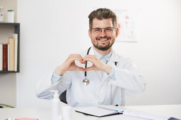 Старший красивый врач показывает жест сердца, бородатый старый терапевт в медицинском халате сидит со стетоскопом в медицинском кабинете и показывает сердце счастливой рукой