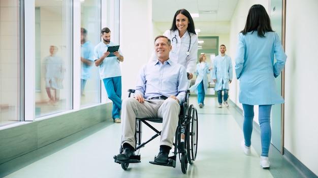 Старший красавец в инвалидной коляске перемещается по больнице с помощью специального медицинского персонала