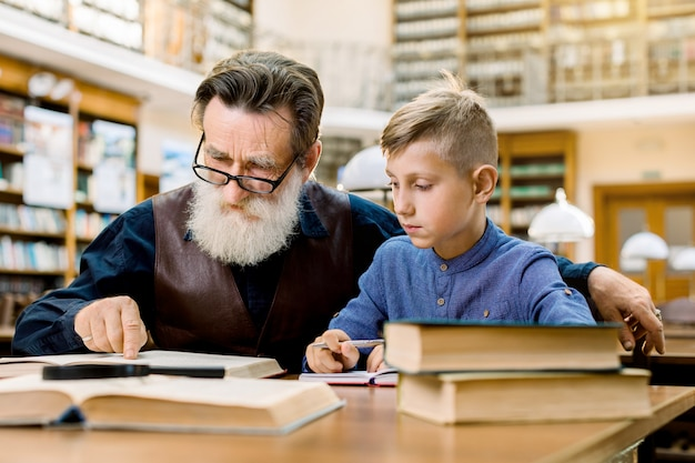 Senior handsome man, reading book aloud to his grandson or student, who is listening to him with attention and making notes. grandfather and grandson in library