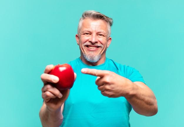 リンゴを持つシニアハンサムな男