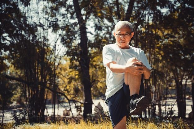 공원에서 스트레칭과 균형 요가 운동을 하는 수석 미남 스포츠맨. 공원 개념에서 건강을 유지하는 방법.