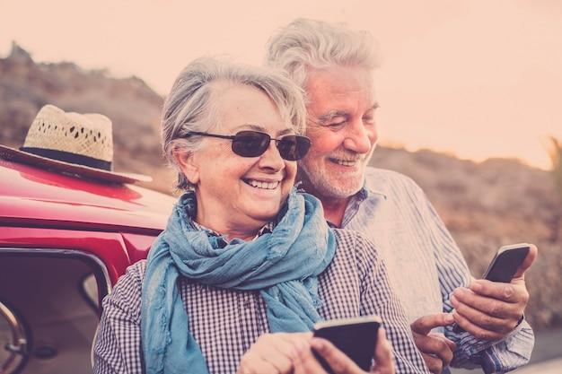 シニアの幸せな陽気な老人白人カップルは、ウェブ上でコンテンツを共有および送信するために、最新のオンラインテクノロジースマートフォンを一緒に使用します