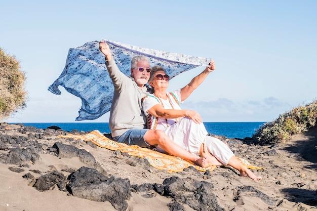 シニアの幸せなカップルは、ビーチで一緒にアウトドアのレジャーを楽しんでいます。バックグラウンドで海。ヒッピースタイルのカジュアルな服と白人の人々の笑顔と愛のための旅行と休暇のコンセプト