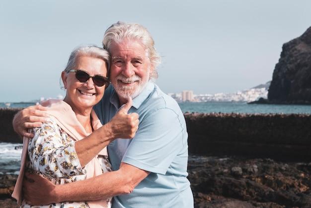 서로 껴안고 여름 방학에 즐거운 바다 여행을 즐기는 수석 행복한 커플