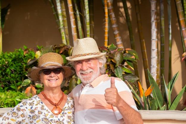 밝은 햇빛 아래 열대 정원에서 여름 휴가를 즐기는 수석 행복한 커플